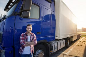 Portrait of middle aged Caucasian trucker in casual clothes standing in front of truck long vehicle with trailer. Transportation services.